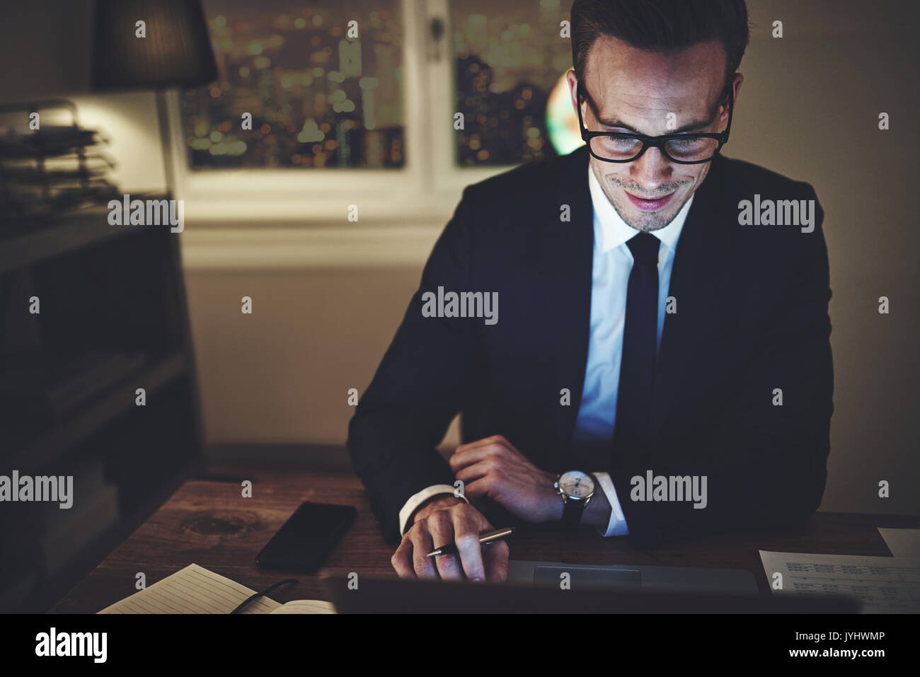 Smiling businessman working on laptop at night sitting in office looking concentrated - Stock Image