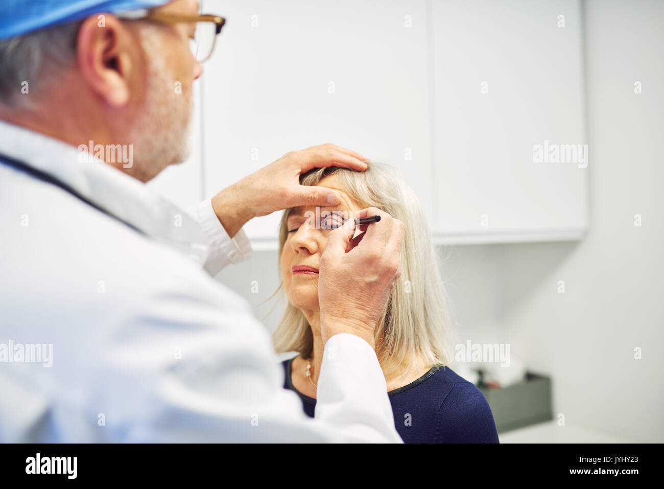 Mature lady in medical office with medic drawing with marker on her face planning anti-age correction. - Stock Image
