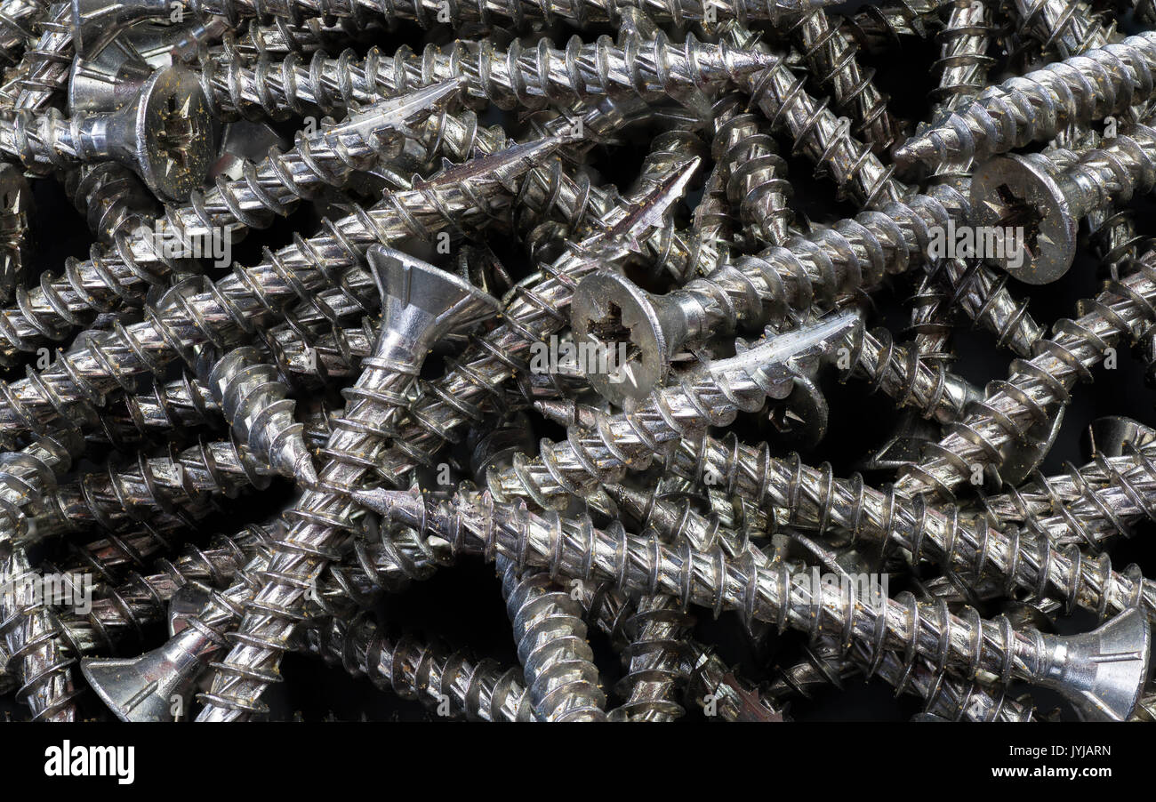 A pile of steel screws all in a bunch with course threads and slotted heads. All in focus set on a barely visable black back ground. - Stock Image