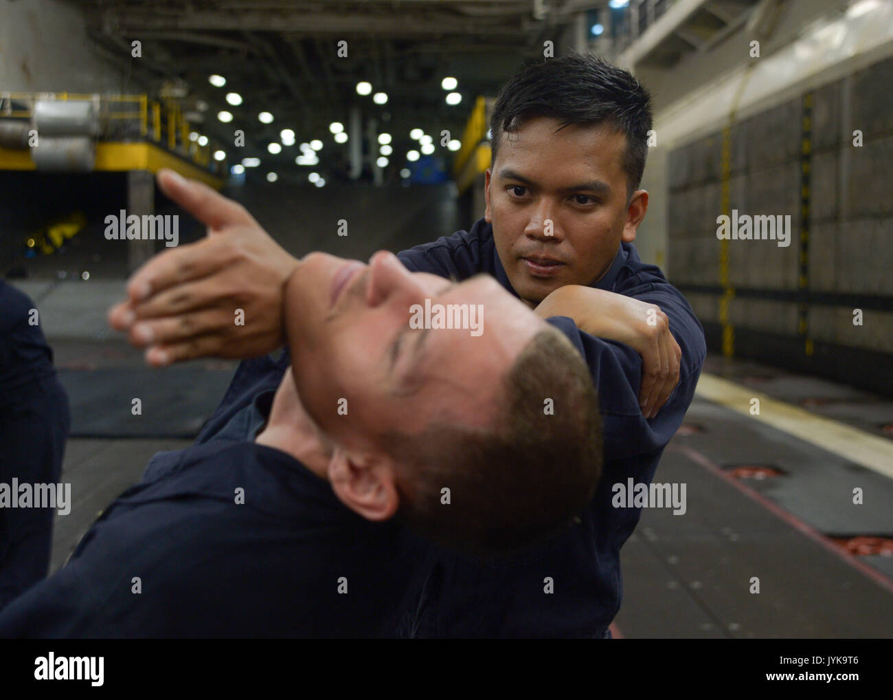 170816-N-NB142-1055 PACIFIC OCEAN (Aug. 16, 2017) Airman Edizon Dizon performs a mechanical advantage control hold (MACH) takedown on Airman Apprentice Jordan Baker during a Security Reaction Force Basic course in the well deck of the Wasp-class amphibious assault ship USS Essex (LHD 2). Essex is underway conducting sea trials and flight deck certifications off the coast of Southern California. (U.S. Navy photo by Mass Communication Specialist 3rd Class Chandler Harrell/Released) - Stock Image