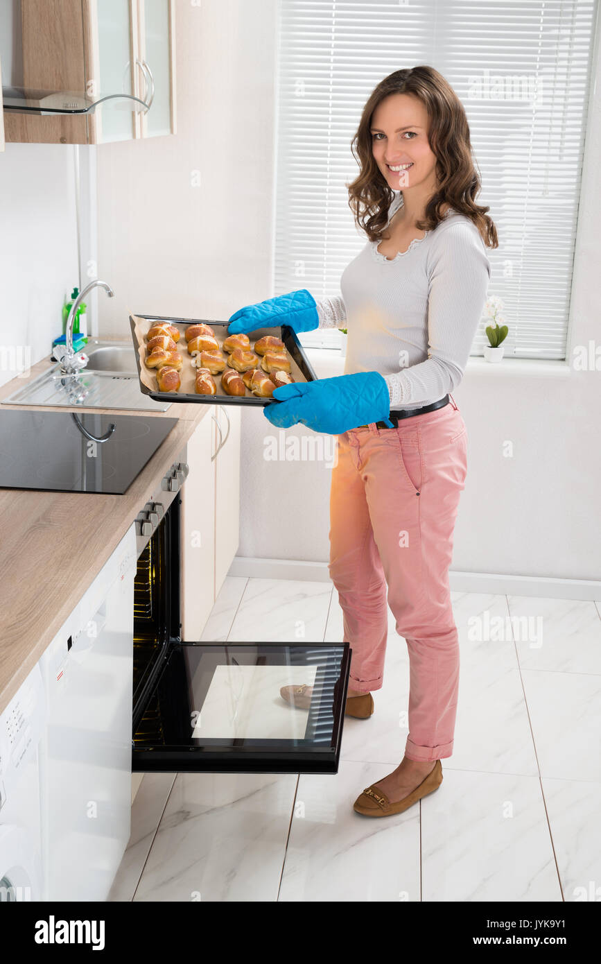 Young Woman Holding Baking Tray With Baked Bread In Kitchen Room - Stock Image