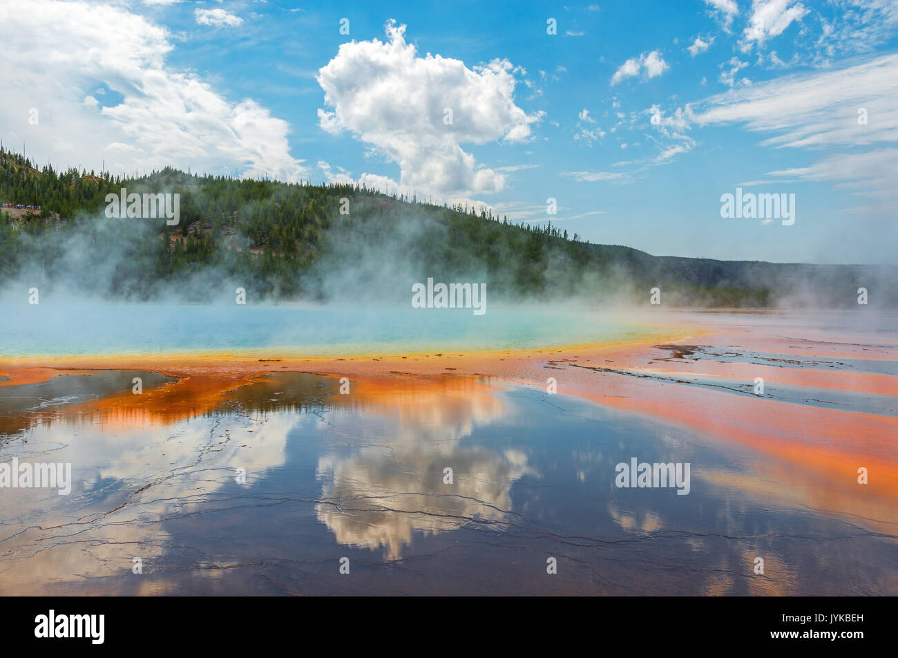 Reflection of clouds on a sunny summer day by the Grand Prismatic Spring inside Yellowstone National Park, Wyoming, USA. - Stock Image