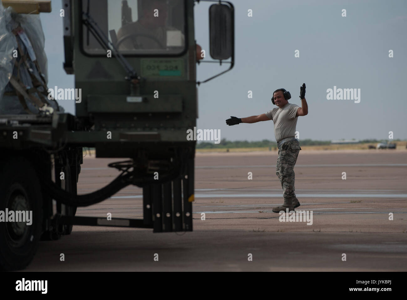 U.S. Air Force Tech Sgt. Jose Ortega, 7th Logistics Readiness Squadron air transportation section chief, guides Stock Photo