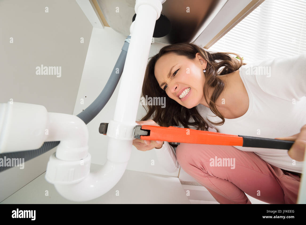 Close-up Of Woman With Monkey Wrench Tightening White Pipe - Stock Image