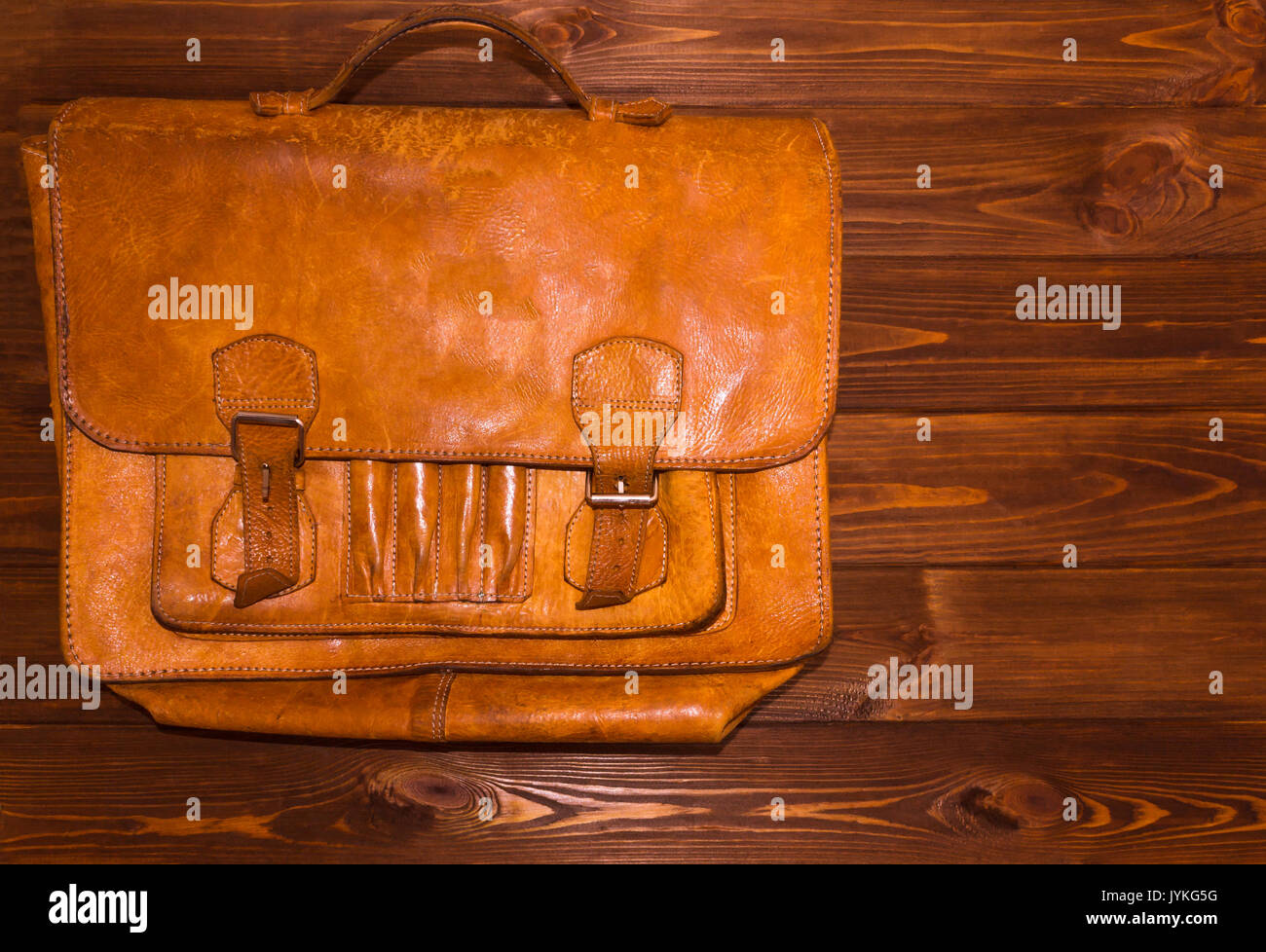 Old leather briefcase on wooden background - Stock Image