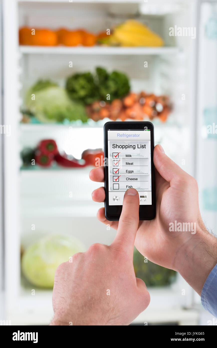 close up of person hands making shopping list on mobile phone display connected to refrigerator