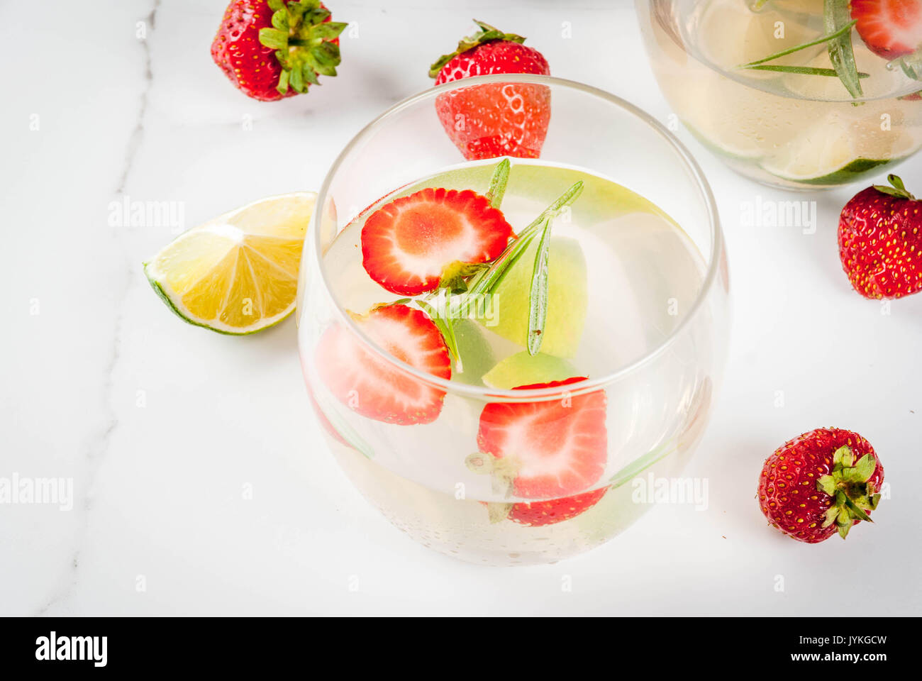 Summer refreshing cocktail. Lemonade with lime, fresh strawberries and rosemary. On a white marble table. Copy space Stock Photo