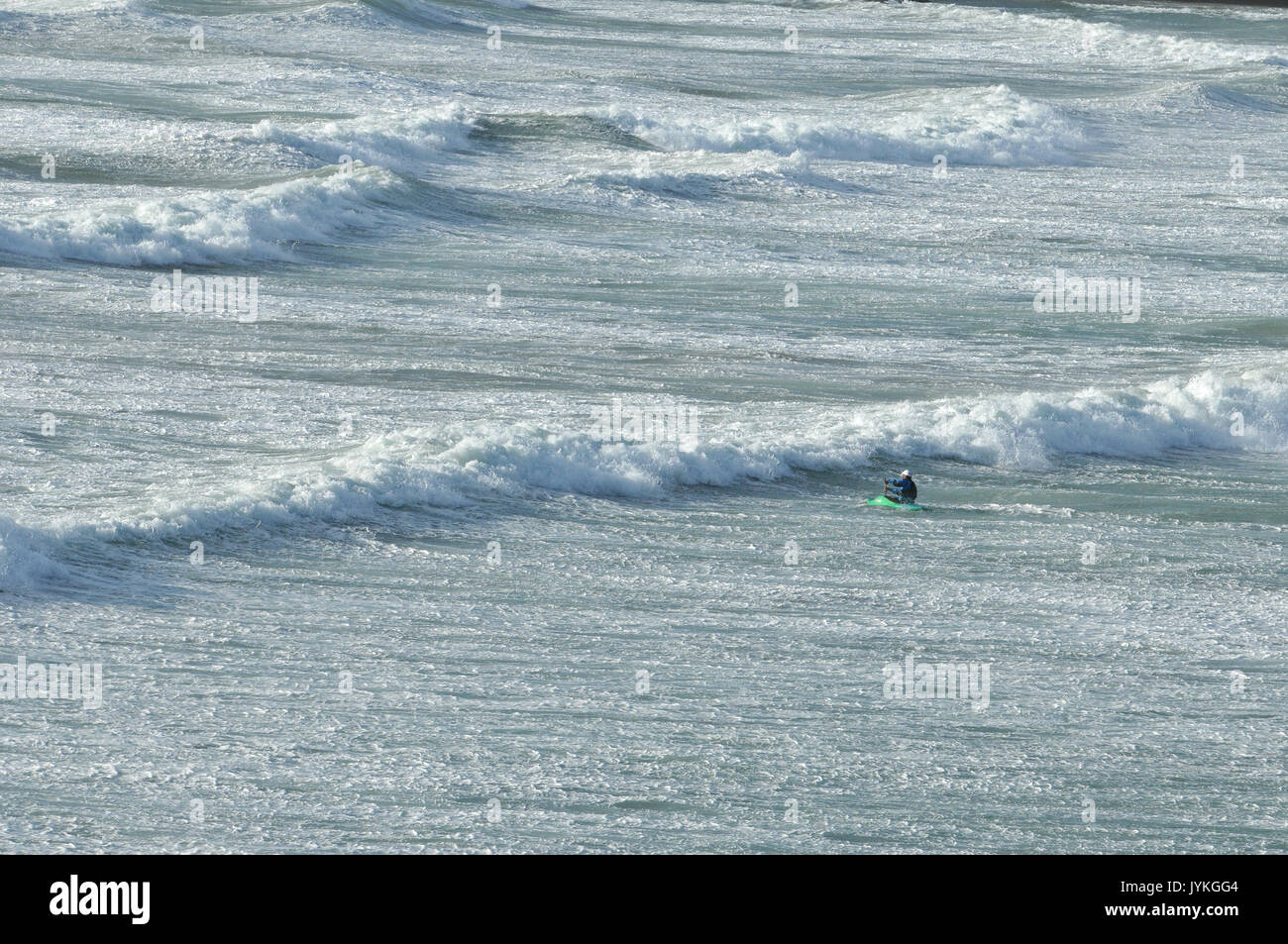 a kayaker paddling against a huge swell rough sea at polzeath in cornwall big waves and breakers canoeists paddlers surf kayaking in the surfing waves - Stock Image