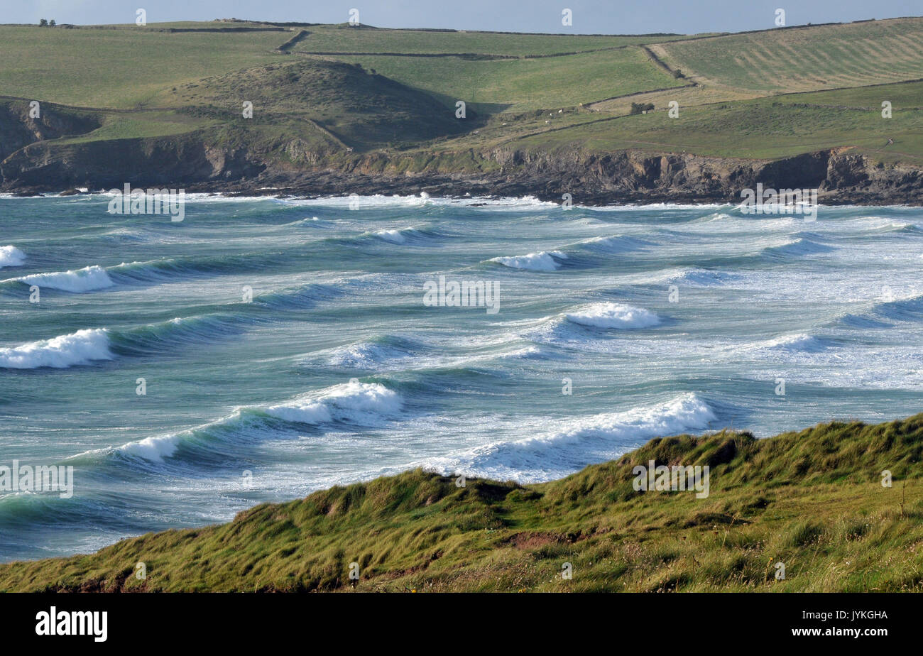 polzeath beach and surfing at the north cornwall coast rough day and seas rough and dangerous sets of waves and breakers rollers white horses sufers - Stock Image