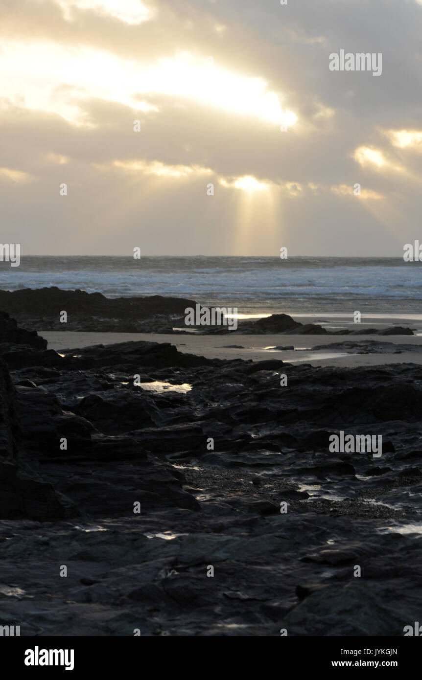 a cloudburst sunset over polzeath beach in north cornwall near the camel estuary rays of light shining down from the clouds over the sea and surfers - Stock Image