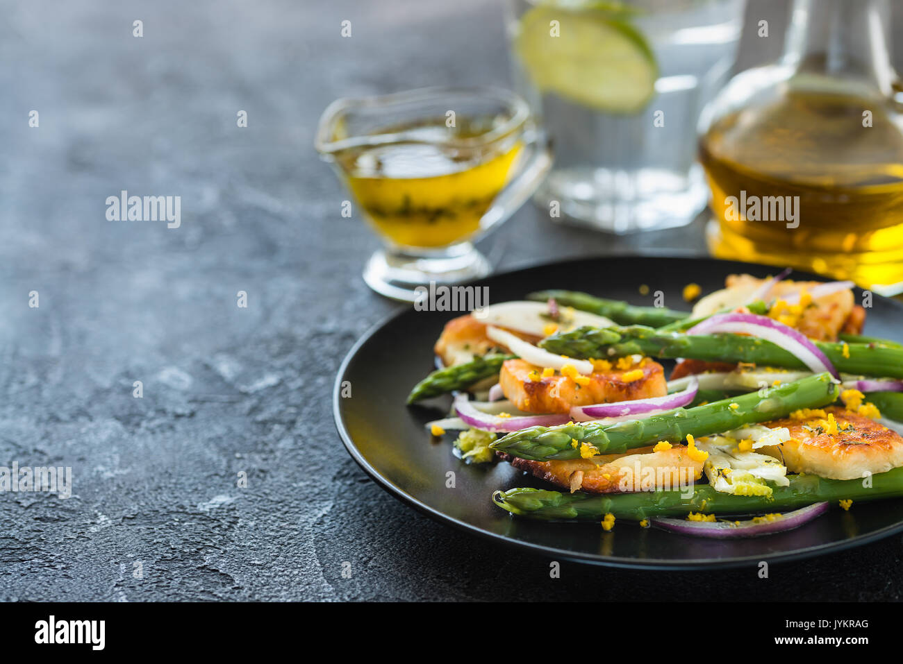 Salad with fried halloumi, asparagus and orange zest. Copy space. Dark concrete background Stock Photo