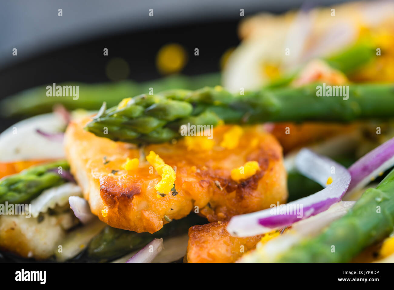 Salad with fried halloumi, asparagus and orange zest. Close up. Dark concrete background Stock Photo