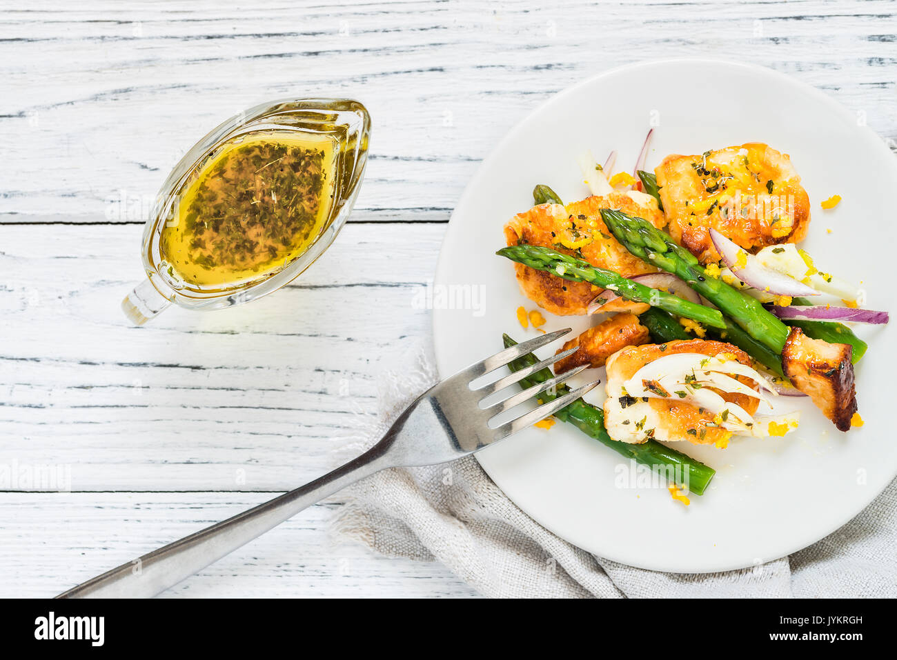 Salad with fried halloumi, asparagus and orange zest. Top view with fork. White wooden background Stock Photo