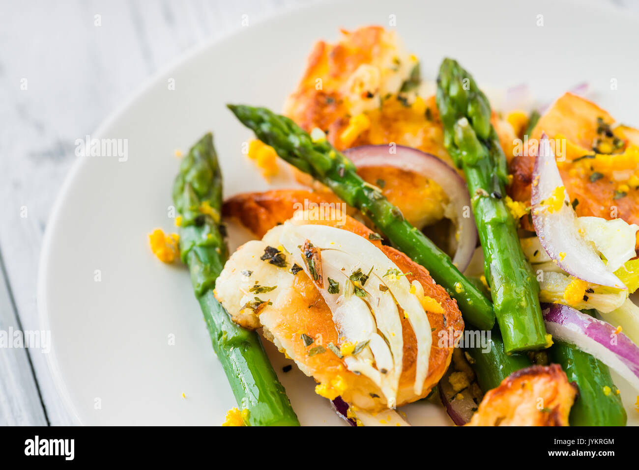 Salad with fried halloumi, asparagus and orange zest. Close up. White wooden background Stock Photo