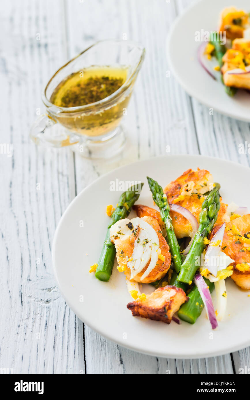 Salad with fried halloumi, asparagus and orange zest. White wooden background Stock Photo