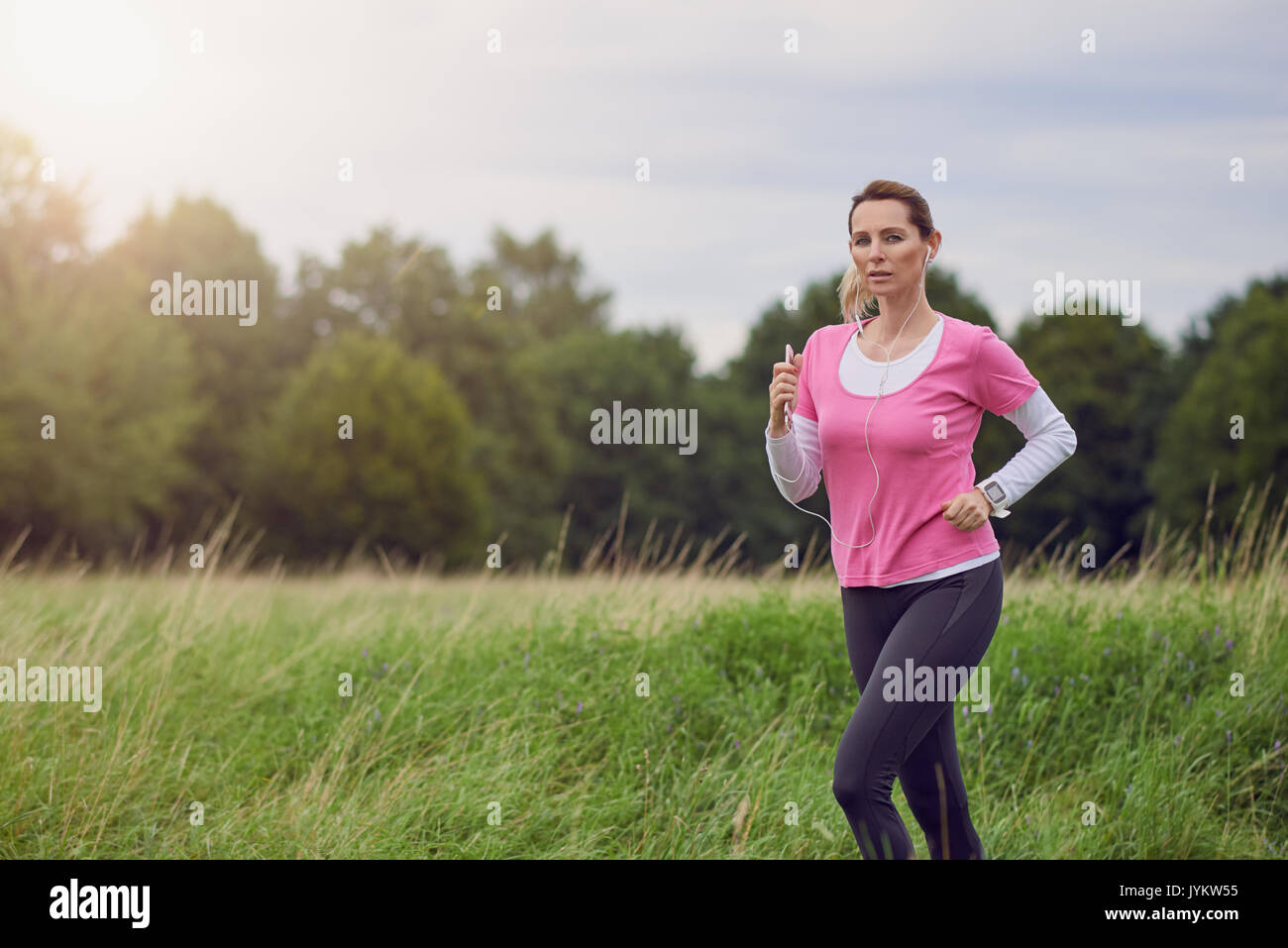 Fit middle-aged woman running through a rural field listening to music on her mobile phone using earbuds looking to the side with a happy smile in a h - Stock Image