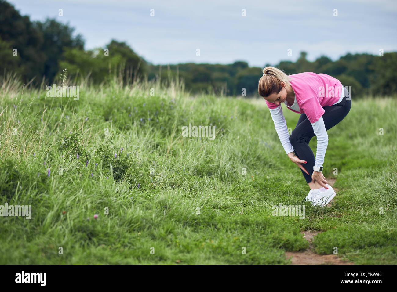 An exercising woman in fit wear while running outdoors, stop to clutch an injured ankle. - Stock Image