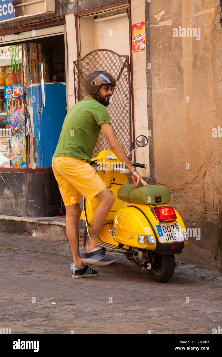 Man getting on yellow motor scooter wearing yellow shorts and green tee shirt in Toledo Spain - Stock Image