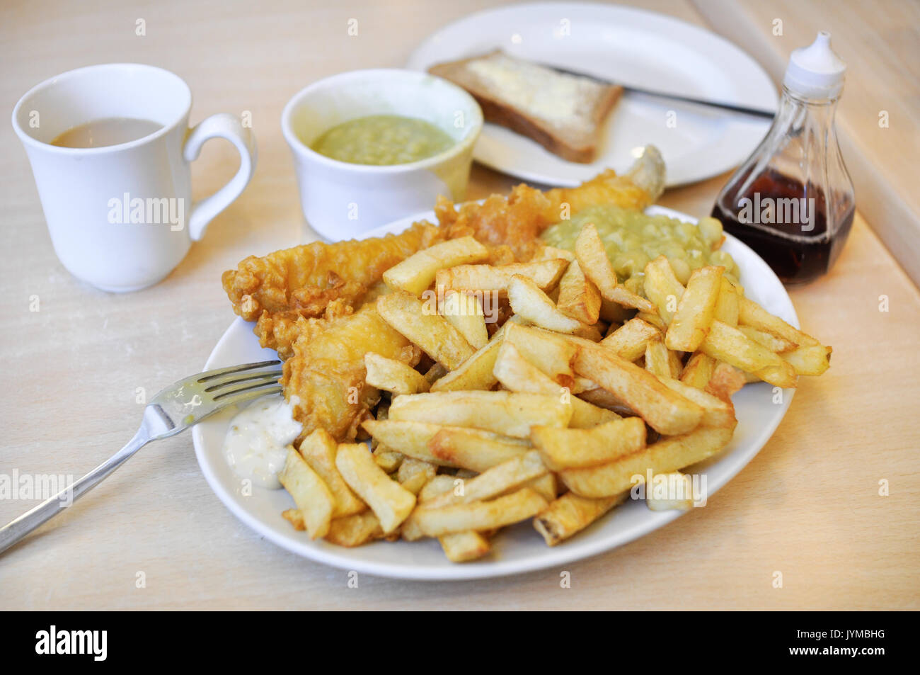 A plate of traditional British fish and chips, with mushy peas, bread and butter, vinegar, tartare sauce, and a cup of tea. - Stock Image