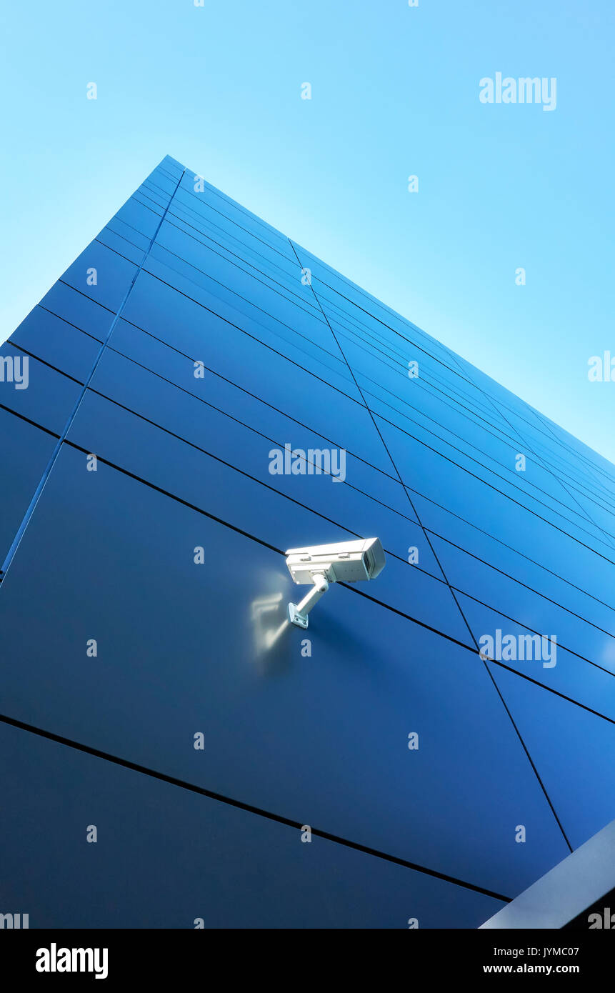 Closed circuit television (CCTV) camera on an office building wall. Stock Photo