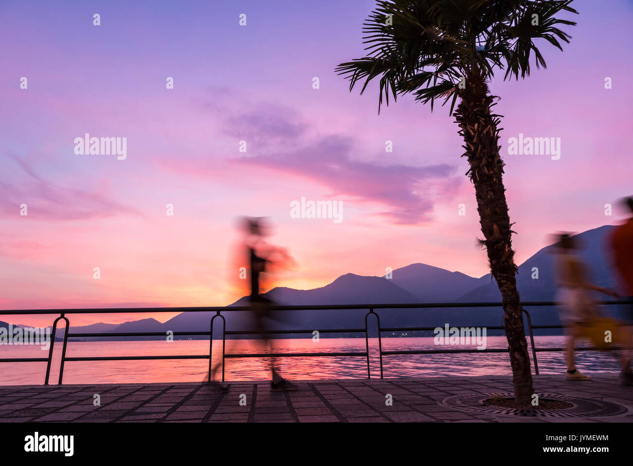 Picturesque foggy sunset at Iseo lake, Lombardy, Italy. Silhouettes of people walking on promenade street in Iseo city - Stock Image