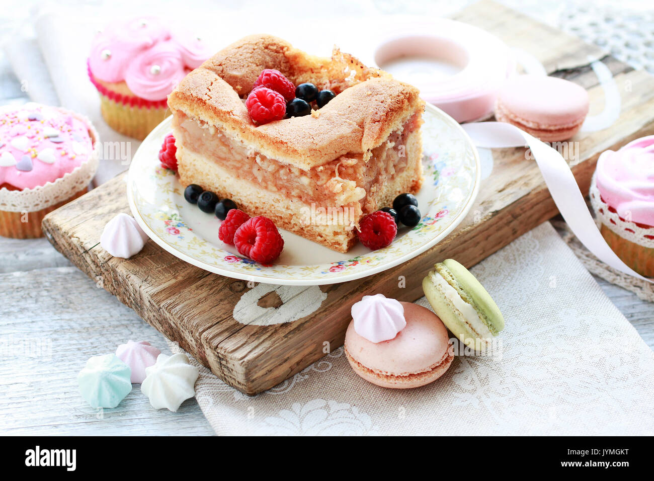 Apple pie decorated with raspberries and blueberries, french macaroons around. Birthday party table. - Stock Image