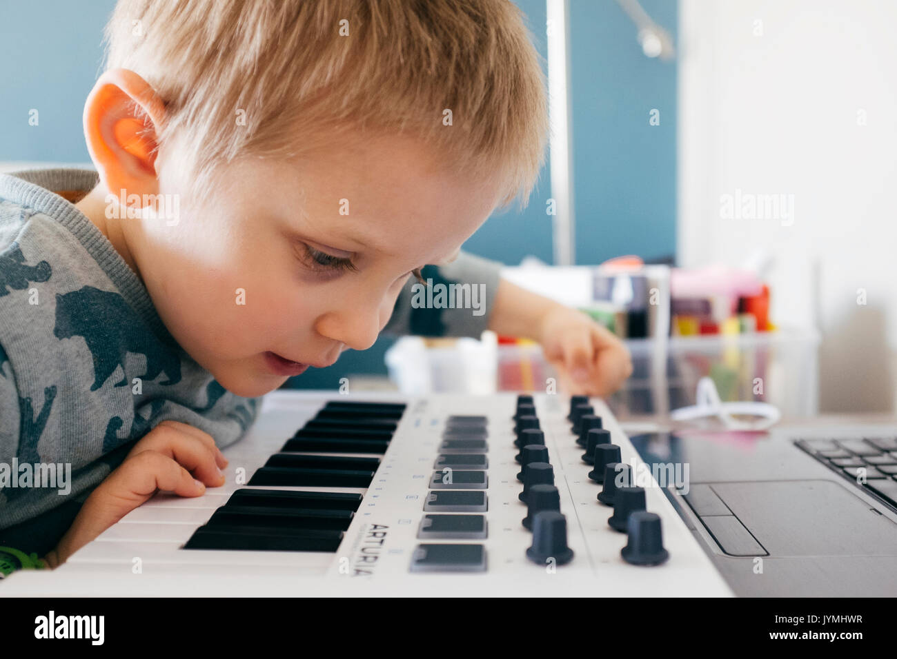 Boy playing with software synthesizer - Stock Image