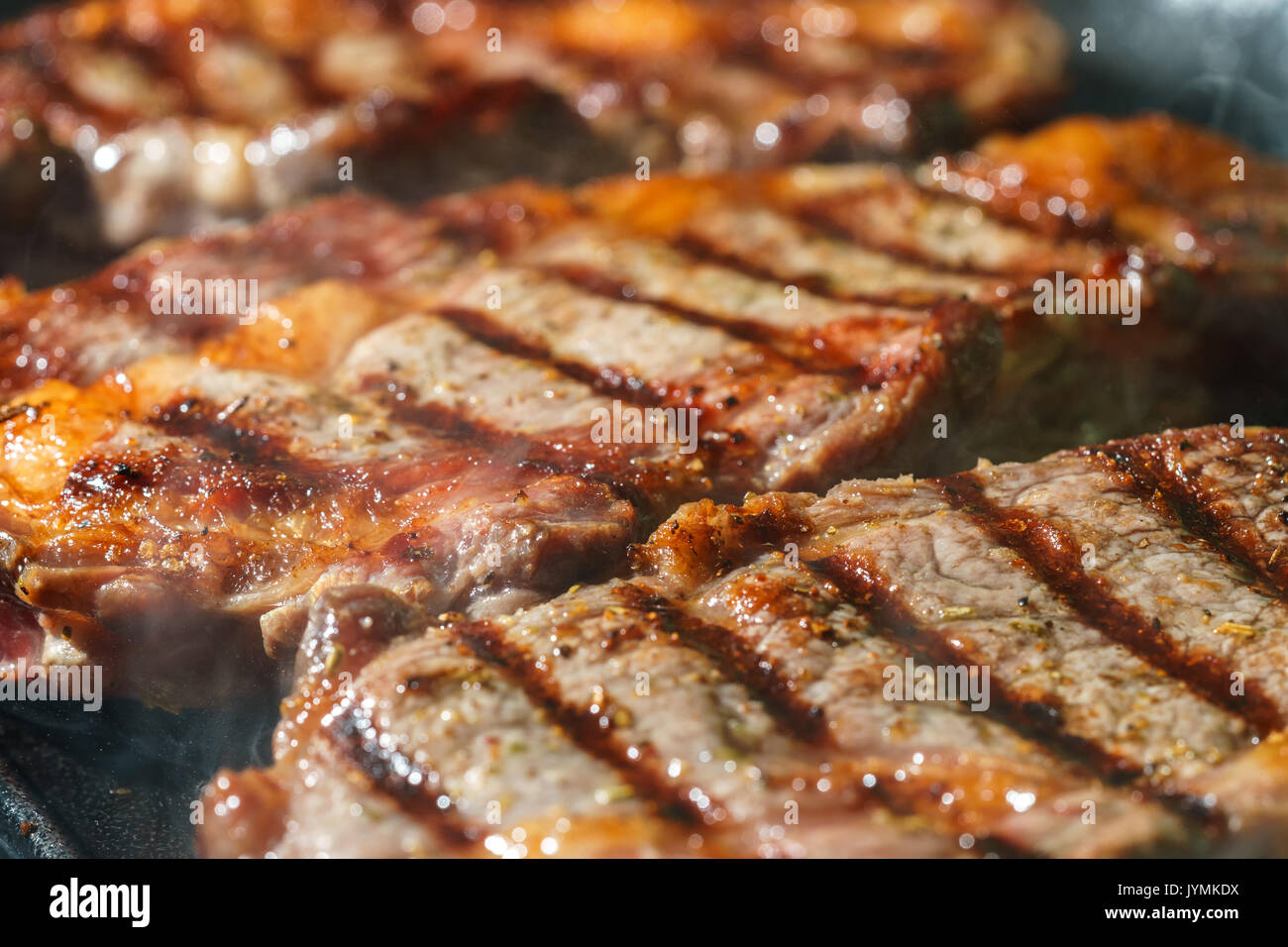 Raw Ribeye Steak with Herbs and Spices, frying on grill pan. - Stock Image