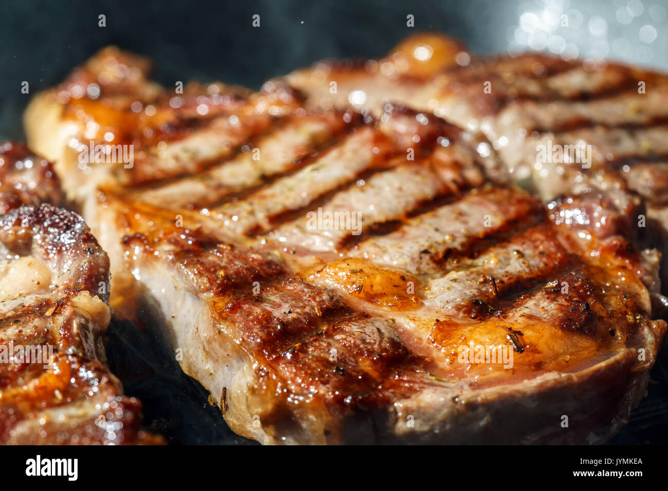 Raw Ribeye Steak with Herbs and Spices, frying on grill pan. Stock Photo