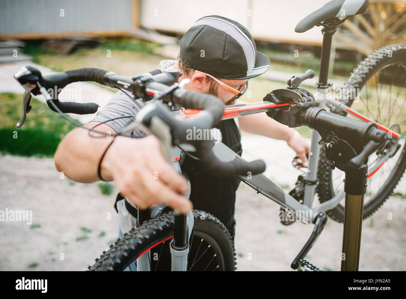 Bicycle mechanic repair bike, top view. Cycle workshop outdoor. Bicycling sport, bearded service man work with wheel - Stock Image