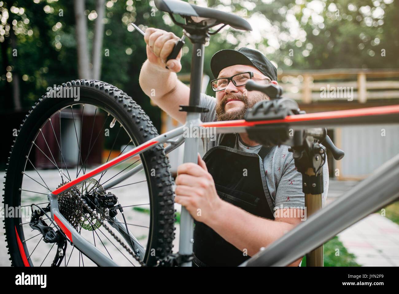 Bicycle mechanic adjusts with service tools bike seat. Cycle workshop outdoor. Bicycling sport, repairman at work - Stock Image