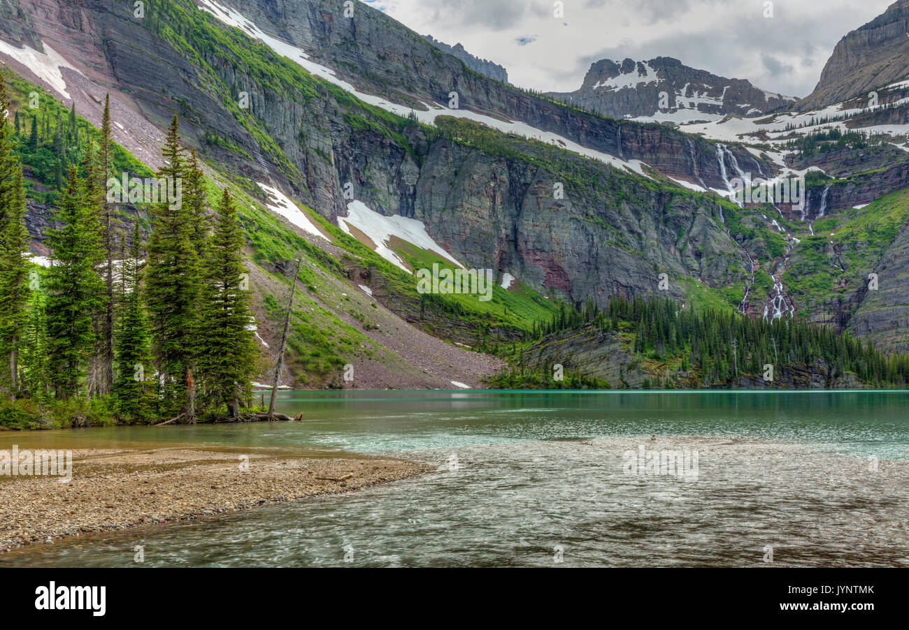 A waterfall flows from Grinnell Glacier into turquoise Grinnell Lake in Glacier National Park, Montana - Stock Image