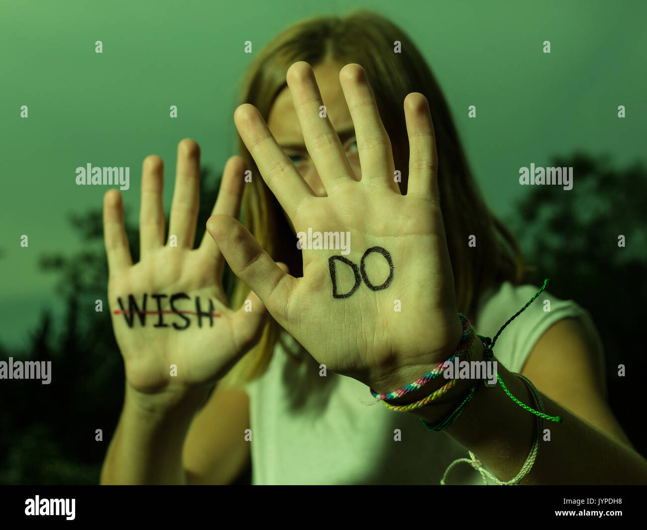 Teenage Girl hold up hands with motivational quotes written on palms. - Stock Image