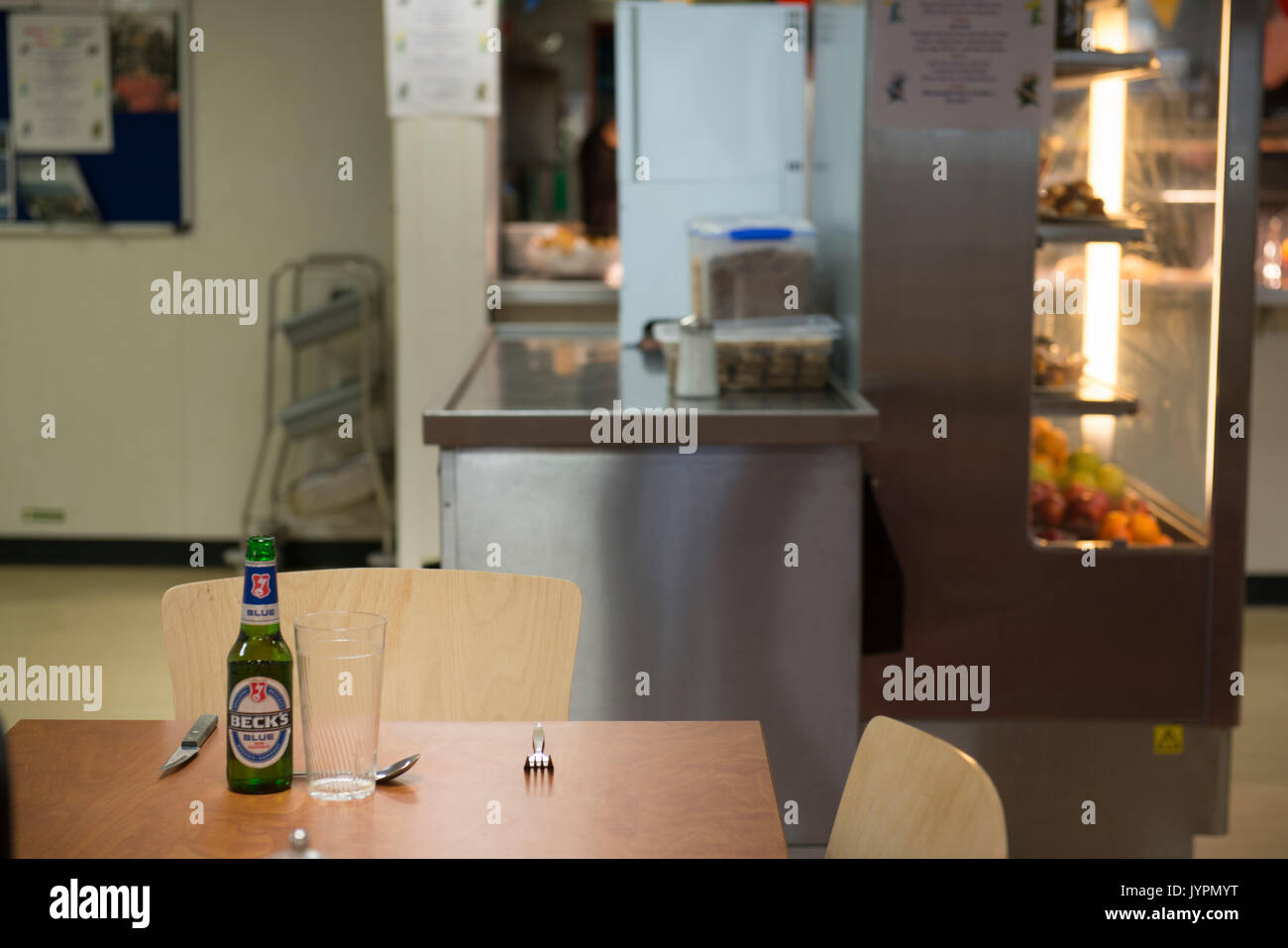 A dinner place setting, with a bottle of backs blue non-alcoholic larger. On an oil and gas rig, in the North Sea. credit: LEE RAMSDEN / ALAMY - Stock Image