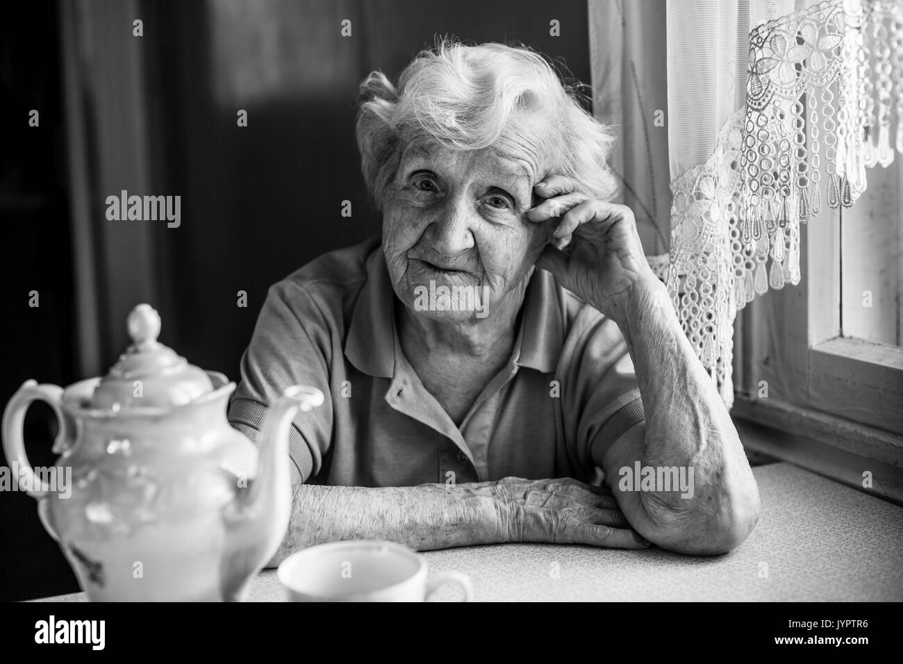 Portrait of elderly woman sitting at the table with tea. - Stock Image