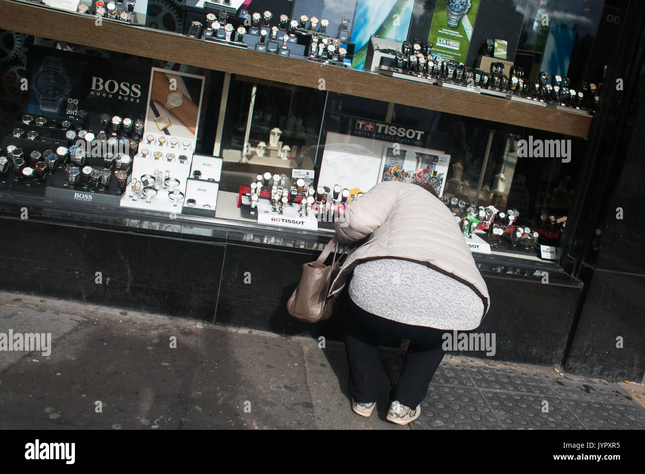 A woman bends over to pick something up in front of a watch shop in Central Edinburgh. - Stock Image