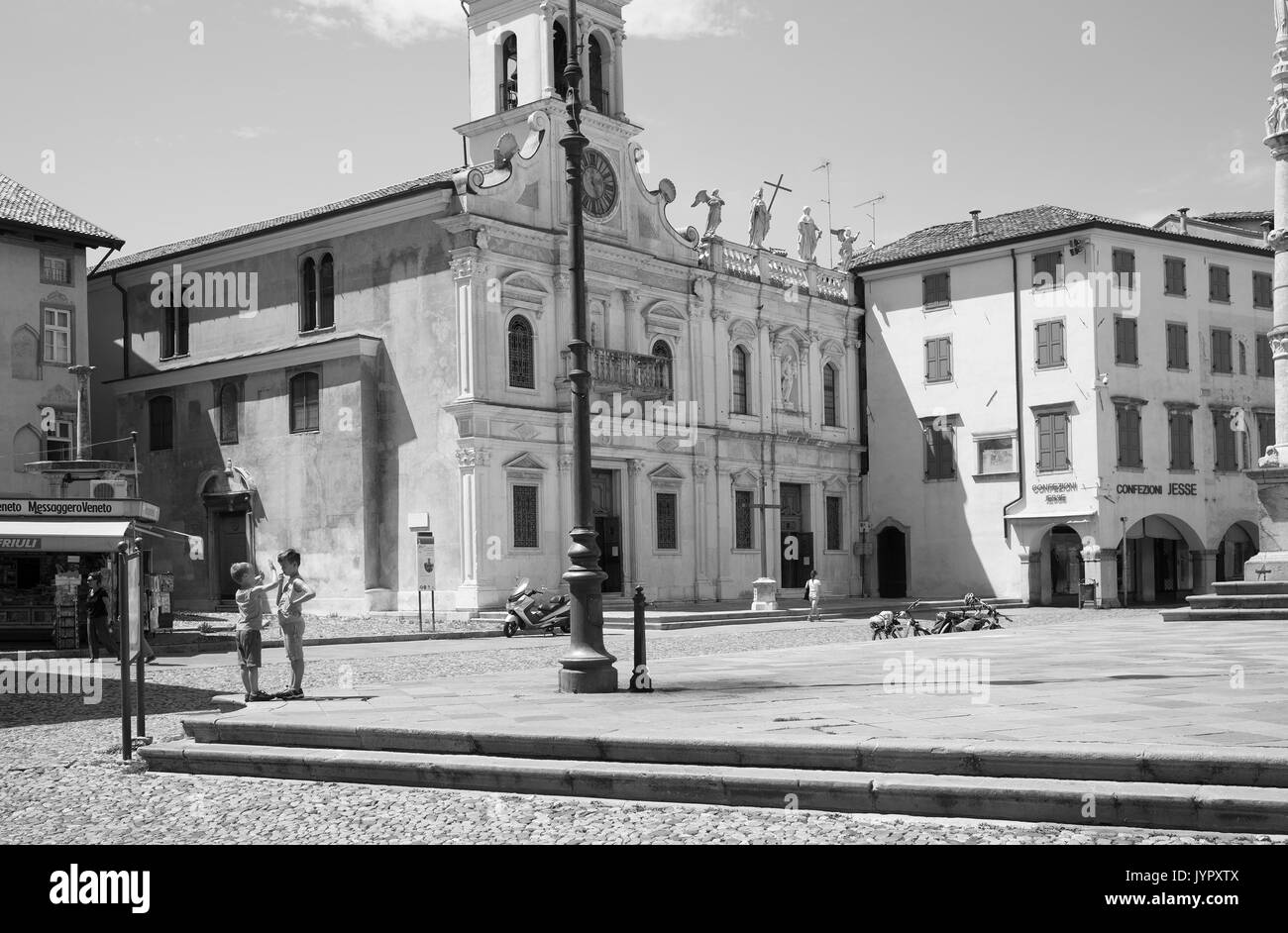 two boys in front of church San Giacomo Matteotti on Piazza Matteotti, Udine - Stock Image