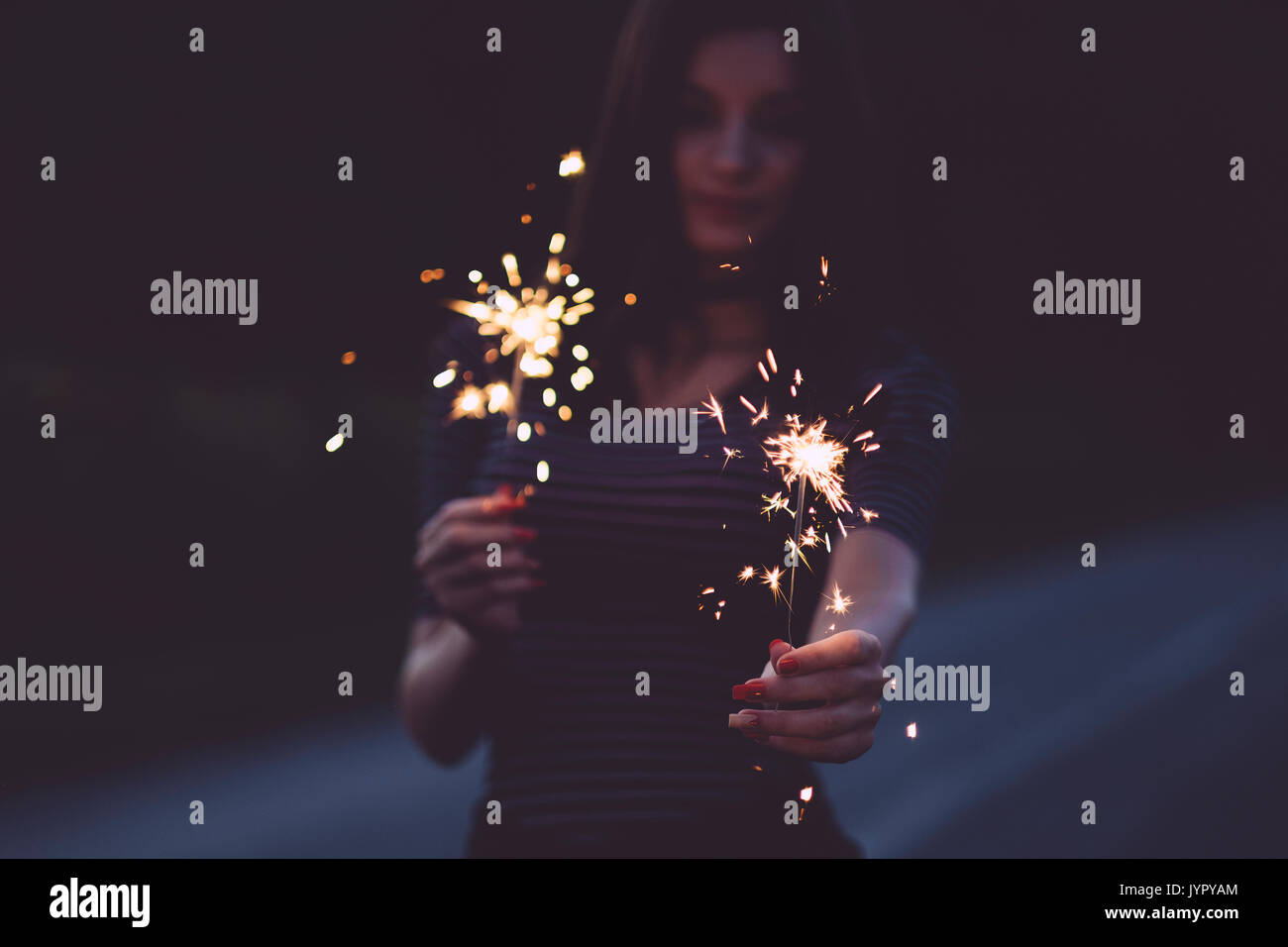 Traveler woman with sparkler on the road - Stock Image