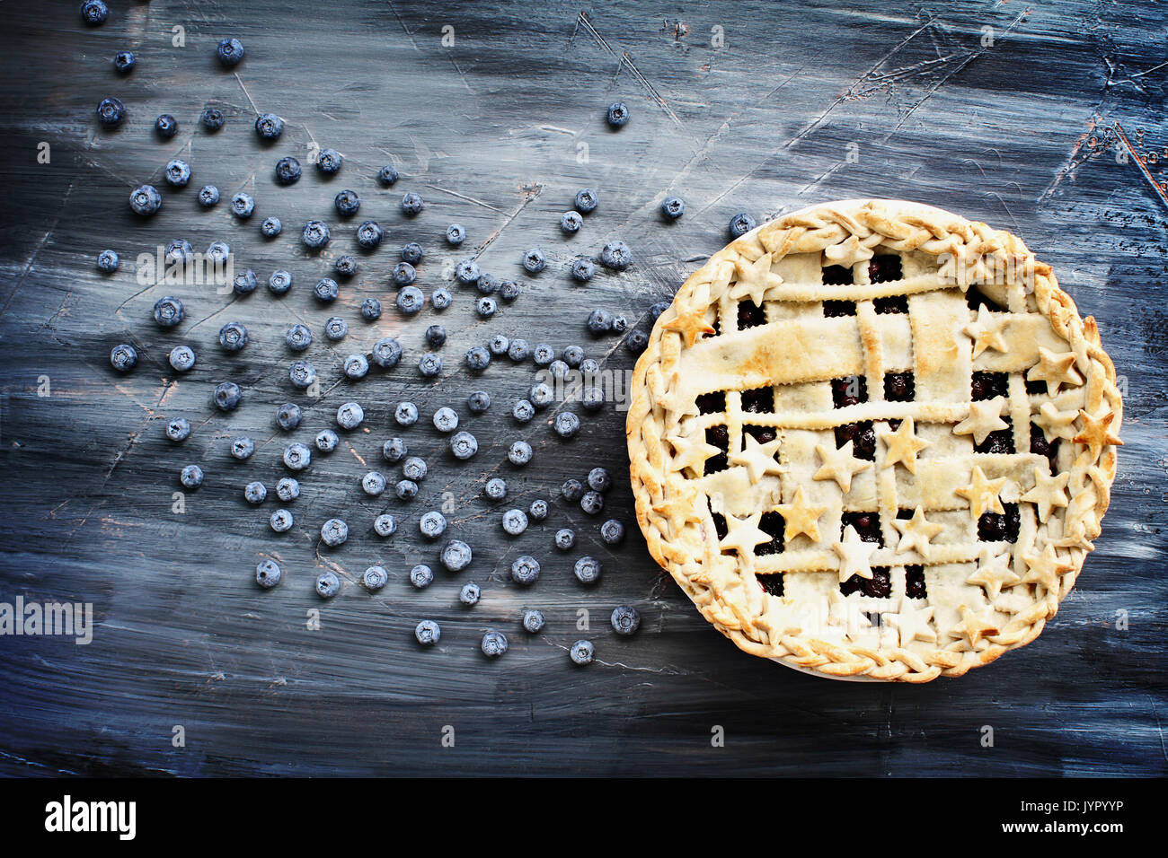Top view of a blueberry pie with lattice and stars crust and fresh berries scattered across artistic wooden background. - Stock Image
