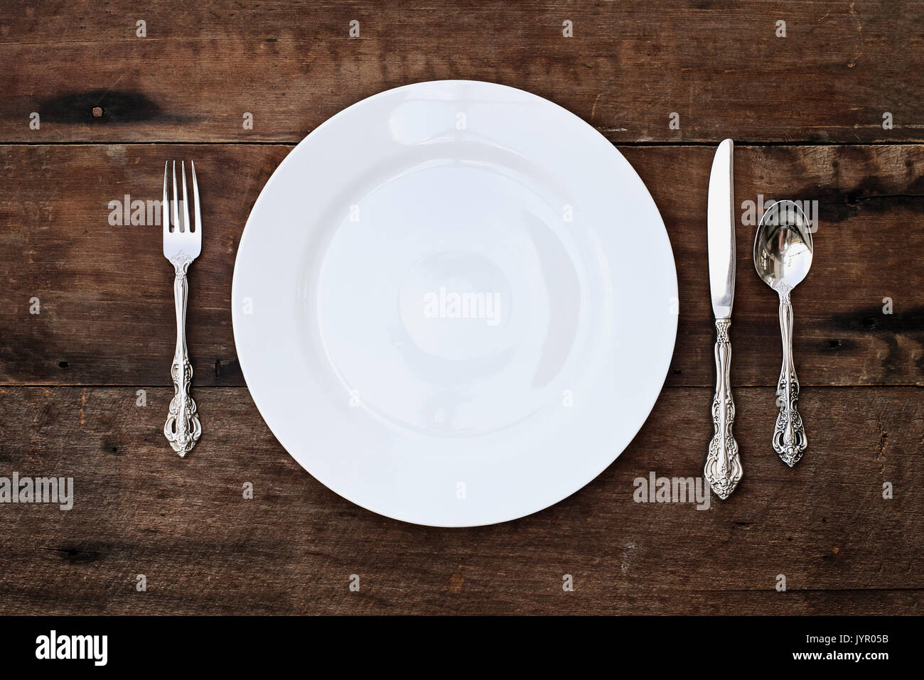 Place setting of a dining set of an empty plate with spoon fork and knife over a rustic old wooden background. Image shot from overhead. & Place setting of a dining set of an empty plate with spoon fork and ...