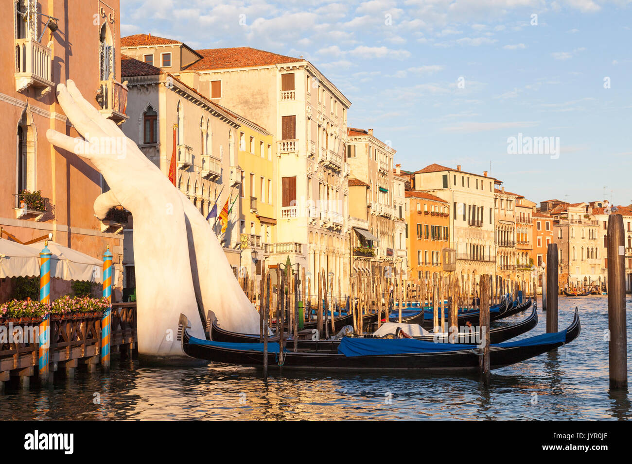 Lorenzo Quinn artwork Support with hands supporting Ca Sagredo Hotel and the Grand Canal at sunset , Venice,  Veneto, Italy with moored gondolas in th - Stock Image