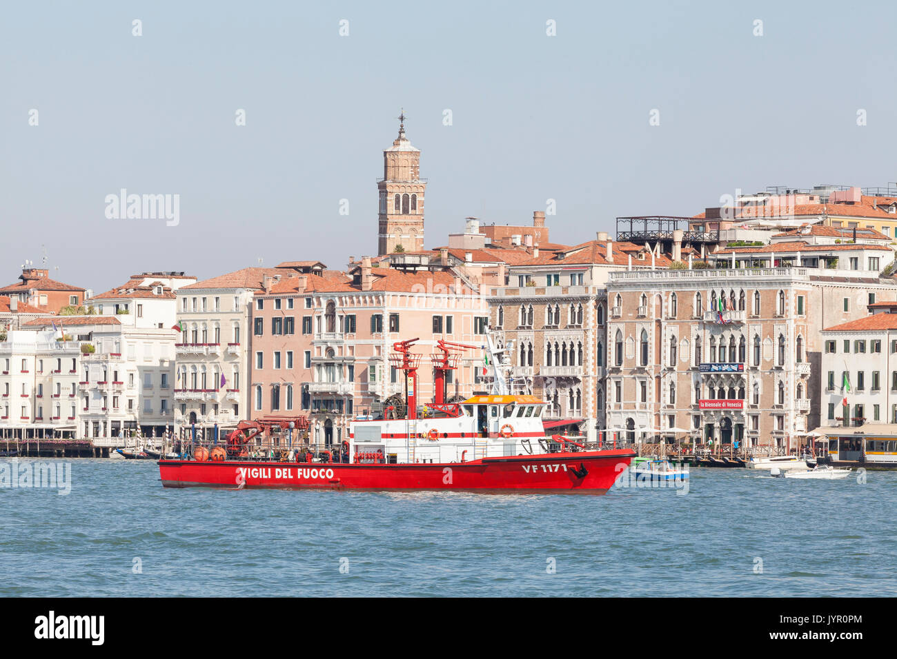 Venetian Vigili del Fuoco or firefighting boat in the Basino San Marco, Venice, Veneto, Italy in front of ancient palazzos. This bright red tender man - Stock Image