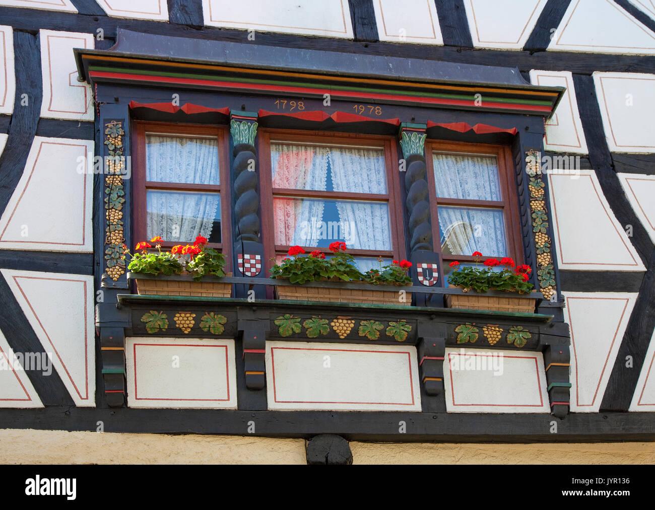Holzschnitzerei, Weintrauben und Weinblaetter zieren einen Fensterrahmen, Fachwerkfassade im Weinort Winningen, Untermosel, Landkreis Mayen-Koblenz, R - Stock Image