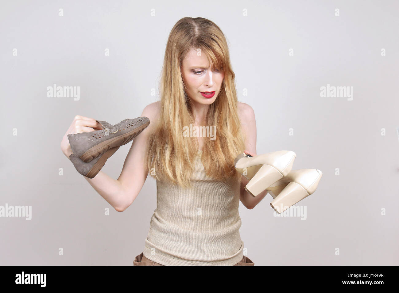 Young woman choosing between high heels and flat comfortable shoes - Stock Image