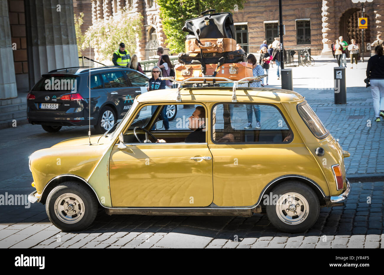 Yellow classic Mini Cooper with old fashioned suitcases strapped to the roof rack going on holiday - Stock Image