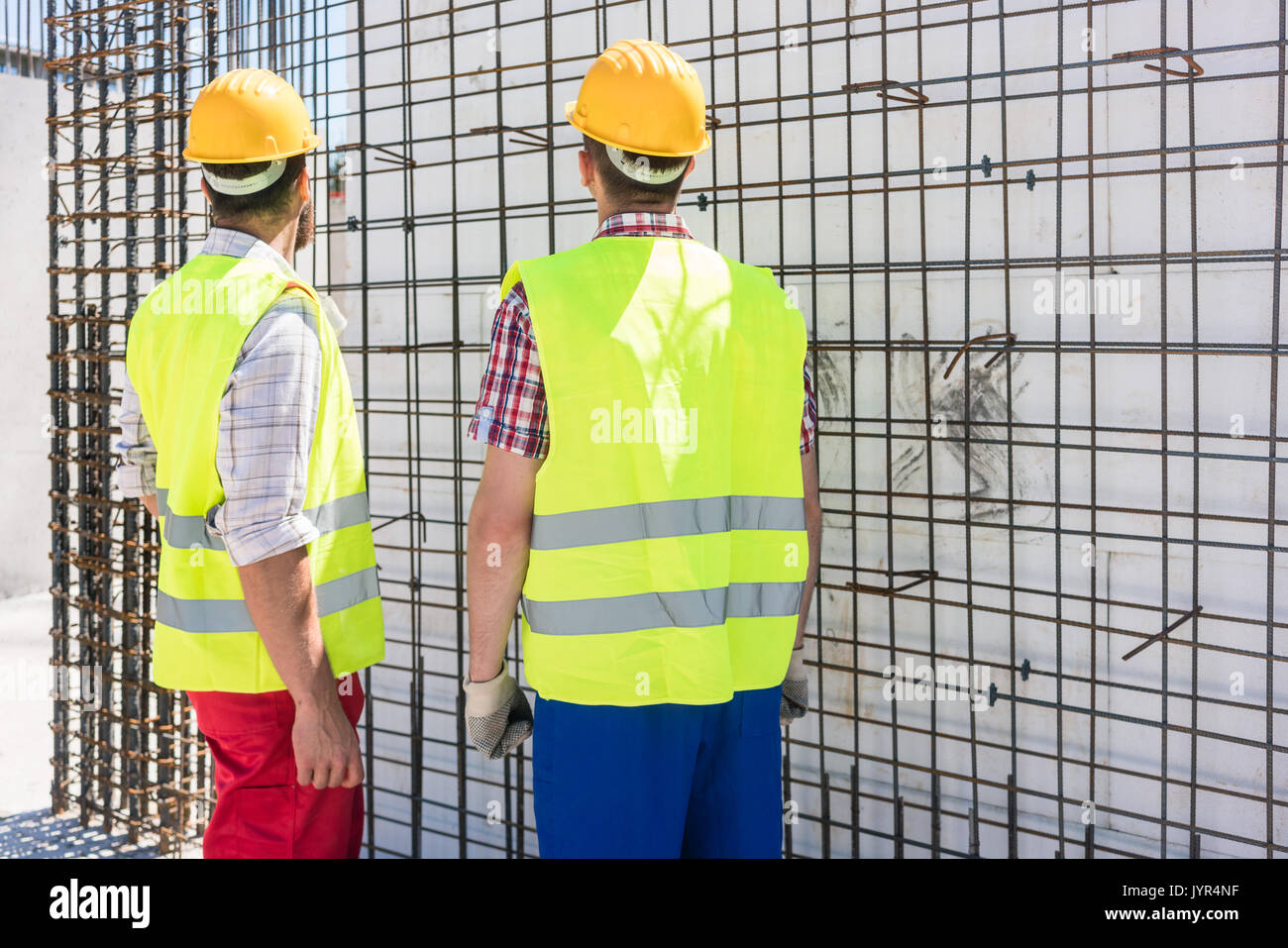 Two workers checking the durability of the steel structure of a  - Stock Image
