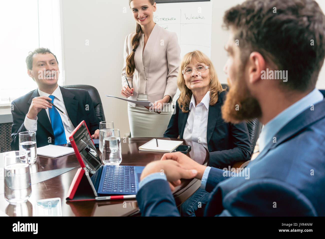 Happy middle-aged managers listening to their younger colleague  Stock Photo