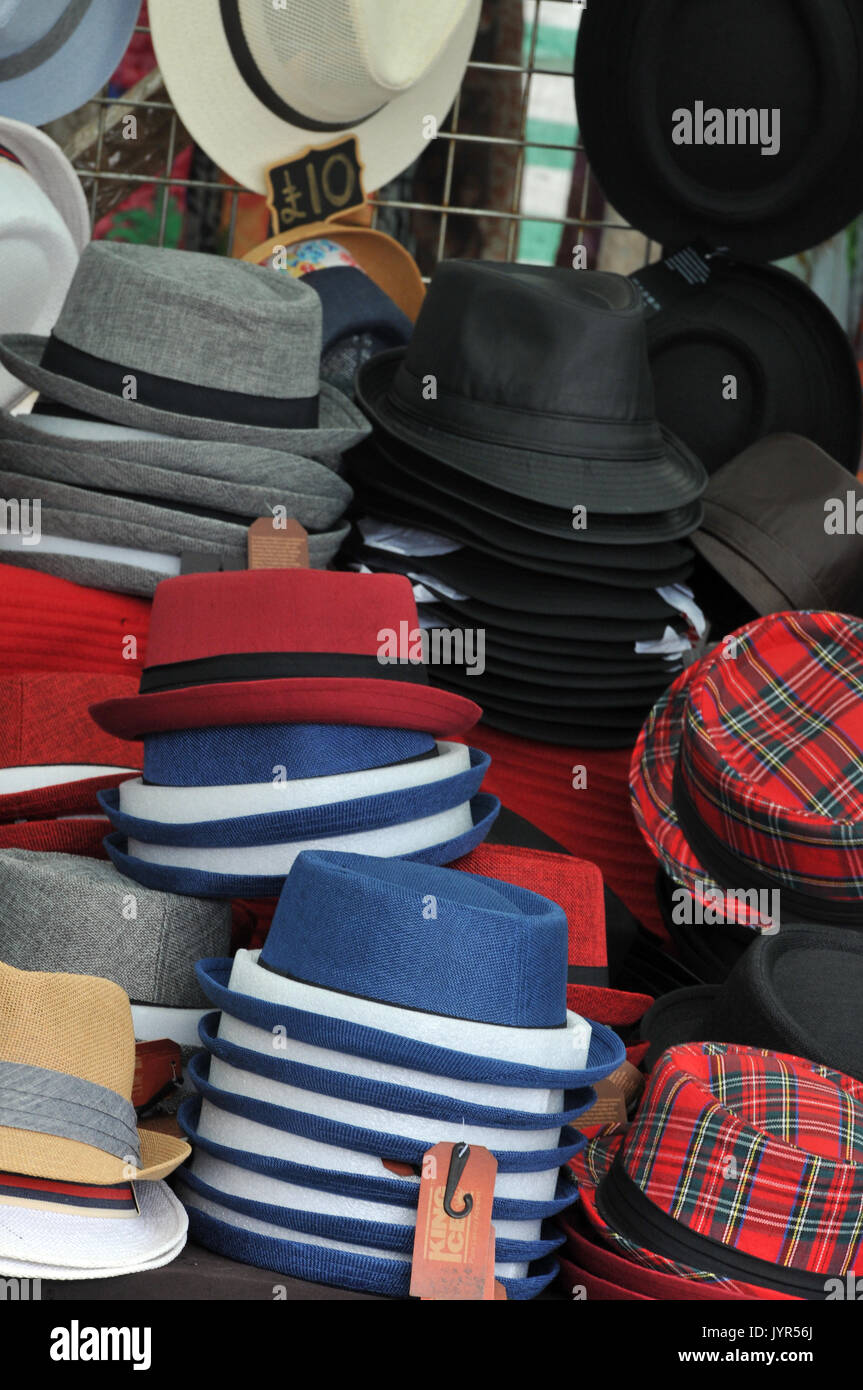 a selection variety of hats for sale trilbys and Stetsons caps and berets pork pies and bowlers at a fair or in the market place stalls hats. - Stock Image