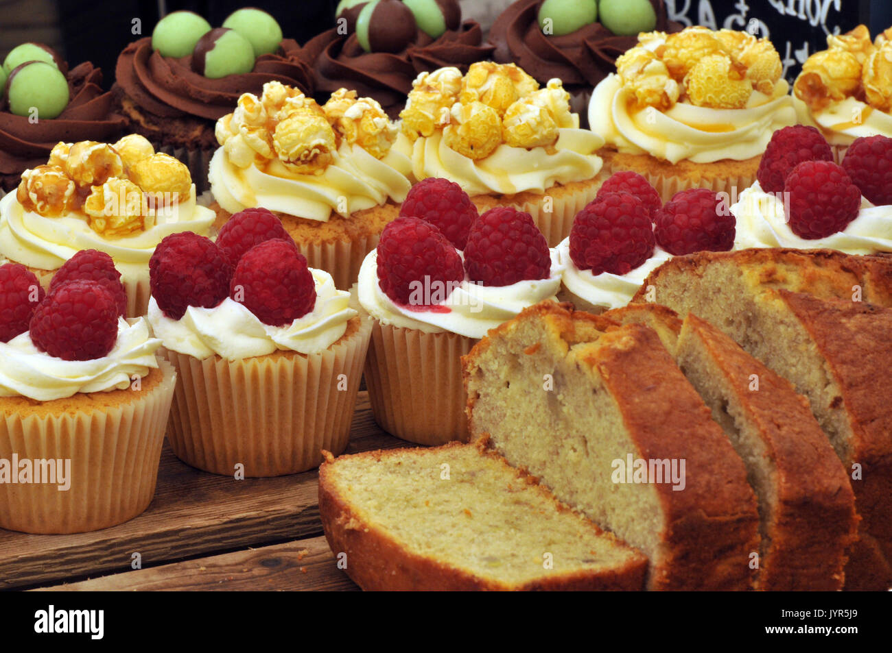 Some gluten free sticky cream and iced icing cakes on display on a cake stand sweet sugary produce for sale very tempting deserts and confections - Stock Image