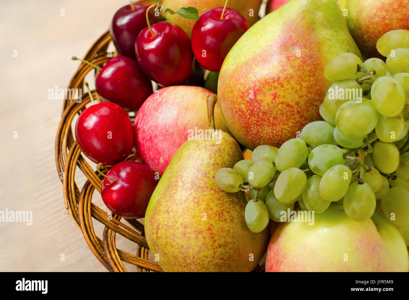 Fruit harvest. Organic fresh apples, pears, grapes and plums in a woven wooden plate Stock Photo